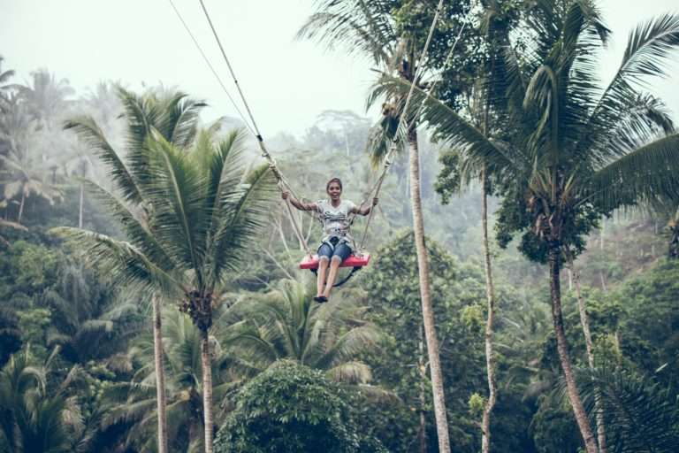 woman using brown rope hammock during daytime
